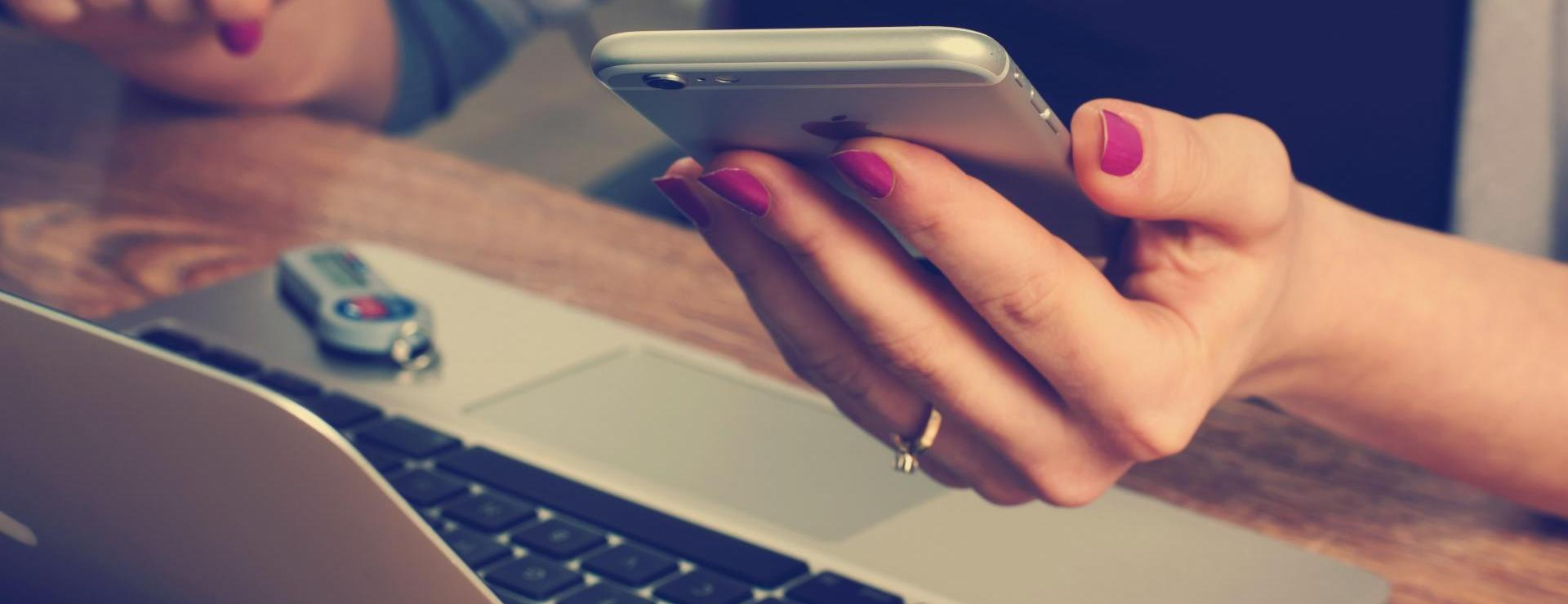 woman's hand holding phone in front of laptop