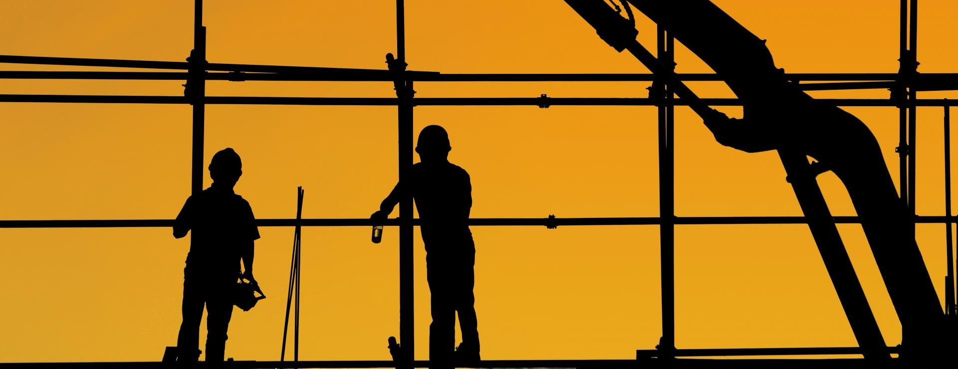 silhouette of two construction workers in front of metal frame with yellow background