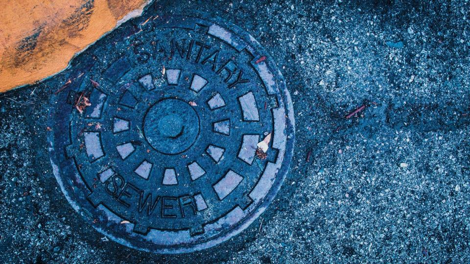Blue manhole cover on pavement