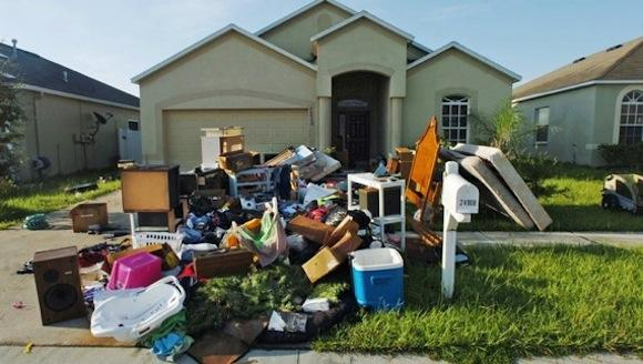 House with pile of junk and debris in front of it