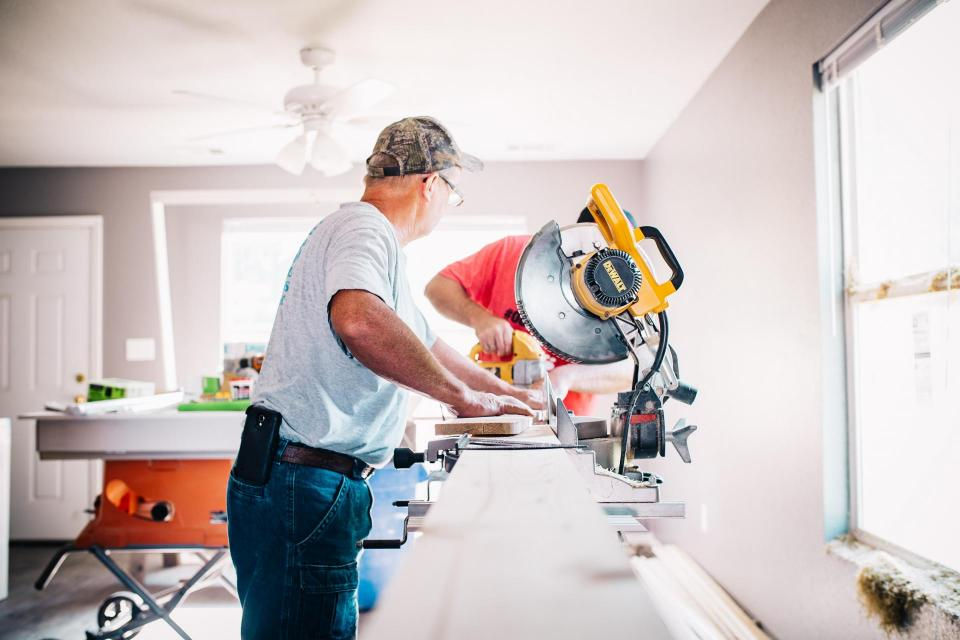 two men working with saw inside home