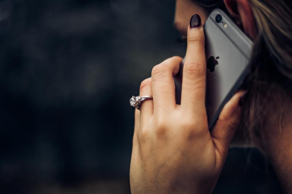 close up of woman holding cell phone to ear