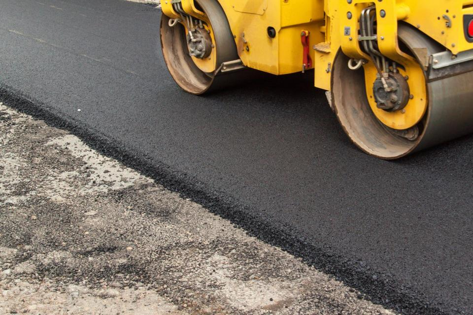 new road being paved by orange paver
