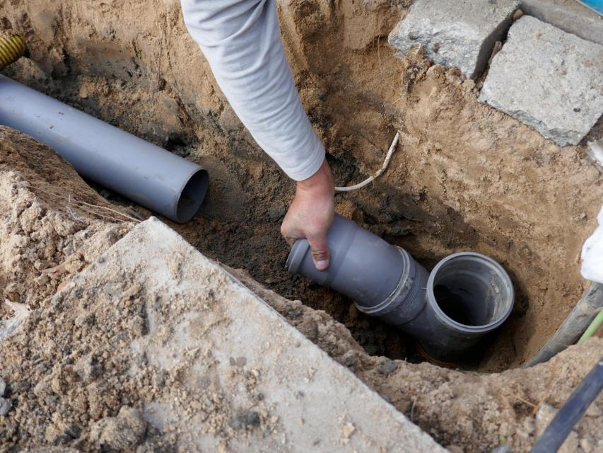 person installing sewer pipe underground